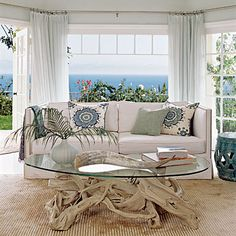Serene View  The rippled silk Tibetan rug, sea-foam walls, and driftwood coffee table hint at the beach beyond. Sheer curtains provide some privacy without completely blocking the view.