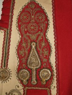 Ivory and red sleeveless vest (Griza me ta Chrysa) with gold thread embroidery. Mesogeia region of Attica, Greece, end of nineteenth or early twentieth century. Wool felt ground, red and green silk braid, gold-colored metallic strip over a yellow core thread. Embroidery type: couching work. http://kent.pastperfect-online.com