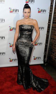 form fitting mermaid dress and tight high and glossy bun. kardashian signature