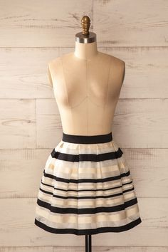 Le noir et l'or vous encerclent de leur charme naturel. The black and the gold encircle you with their natural charm. Black and beige striped pleated skirt www.1861.ca