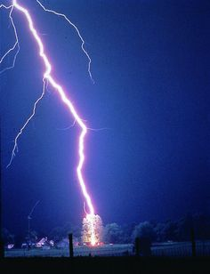 Lightning hits a tree. See the streamer on the left coming up from a pole. It is not connected to the main leading channel.
