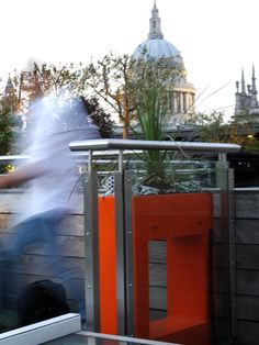 An #orange #hollow #powder #coated #steel #planter on a river terrace with St Paul's Cathedral in the background and client in motion