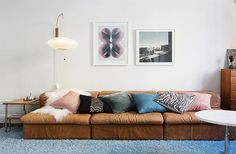 Great cushions and prints, and a beat up old leather sofa.