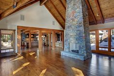 Large great room with Montana Lodge stone fireplace, timber framed tongue and groove Pine ceilings, and hand-distressed Hickory floors.