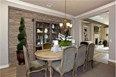 Stacked stone transforms one wall of this Dining Room. The well-chosen table and upholstered chairs complete the color palette. From Taylor Morrison Homes, Trovita Estates near Phoenix.