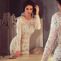Heavily beaded evening dresses with long sleeves like this can be recreated by our US dress design firm. We specialize in making similar replicas of haute couture dresses that are less expensive for those women who are on a budget and can not afford the original. Formal evening gowns like this could be worn for weddings or other special occasions. Get pricing on any dress you love from the internet when you email us directly.