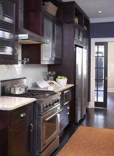 espresso stained kitchen cabinets with white granite and dark floors