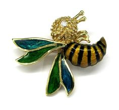 Ladies 14kt yellow gold diamond and enamel bee estate pin. Pin contains 1 brilliant round cut diamonds weighing approximately .02ct. Pin has blue and green enamel color on the wings and yellow and black enamel color on the body. Pin weighs 5.91 grams of 14kt yellow gold.