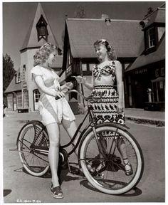 Virginia Mayo rides a bike. Vera-Ellen offers chocolate.