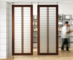 Modern interior room divider featuring fixed Canaletto Walnut Frame with Aluminum and Frosted Glass Panel
