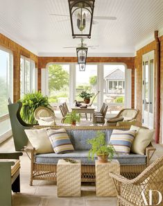 A porch's antique wicker sofa is topped with striped pillows in a Groundworks fabric | archdigest.com