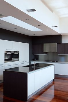 Rich dark framing cabinetry provides modern contrast to central white cabinets & ceiling detail