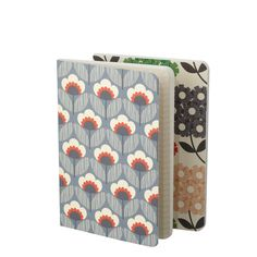 Orla Kiely: Set of two layflat notebooks, one ruled, one blank. 80 pages each book. Two covers - Poppy Meadow design in cornflower colourway, and Multi Rhododendron design in graphite colourway. Signature stem print end pages. Layflat binding for ease of use. For use with Orla Kiely B6 folio or on their own as slim and portable pocket notebooks.