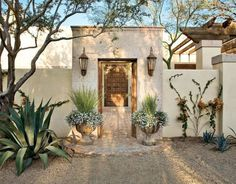 Spanish colonial entry courtyard . Features a cantera stone gate and hand-carved lion shield Photo: Mark Lohman
