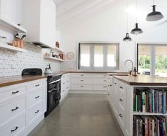 polished concrete flooring, wood countertop, white cabinets