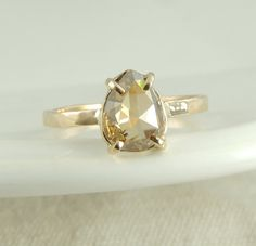 This ring is made of solid recycled 14k yellow gold and a beautiful translucent/ champagne colored pear shaped diamond. The diamond has been