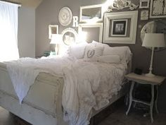White chic bedroom. I love the arrangement of frame's & mirror's above the bed.