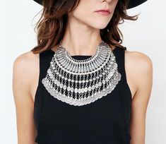 Silver-tone metal chainlink fringed collar necklace with metal coin detailing and hook and eye closure.