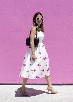Flamingo skirt with a white top, black leather quilted 2.55 bag, pointed toe cork heels, pink sunglasses at a pink wall on Melrose Ave in Los Angeles