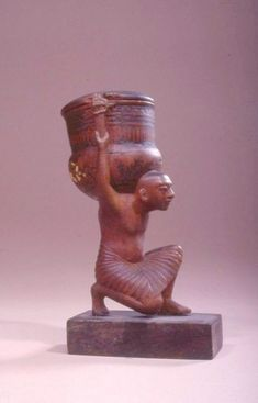 Cosmetic Vessel of a Servant Carrying Unguent VaseThis wooden...