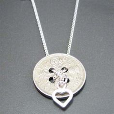 button sixpence in this pic...but use any coin of significance.  Love the heart charm, too