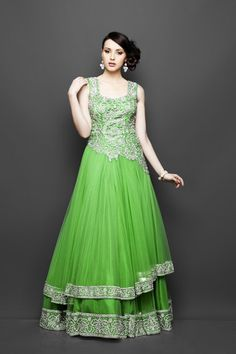 This Green color Indo Western bridal gown with a long as fitted asymmetrical bodice which has silver zircon, green stones & silver ornate embroidery is in net fabric. The flair has layers of net edged