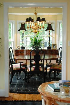 .I love the clean uncluttered look of this dining room.  Also, the look of the shades on the chandelier and the black lamps on the sideboard.