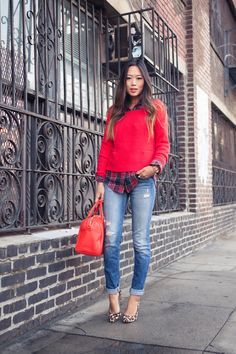 Red sweater with layered red plaid button up underneath. Jeans and heels. | Street Style