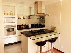 Projetado pela arquiteta Daniella Simonassi, esta cozinha é de um apartamento em Serra (ES). A bancada que abriga o cooktop leva um tampo de granito preto. A marcenaria feita é de MDF branco e a parede recebeu um revestimento que imita pastilha.