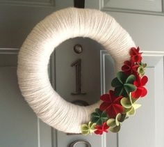 Yarn wreath with felt flowers. This would show up against our black door.