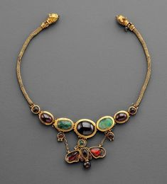 Hellenistic Gold, Garnet and Emerald Butterfly Necklace, 2nd Century BC The butterfly is by no means simply a decorative motif, but a symbol of eternal love. It represents Psyche, the personification...