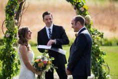 bride laughs during vows at outdoor ceremony under floral arch @myweddingdotcom