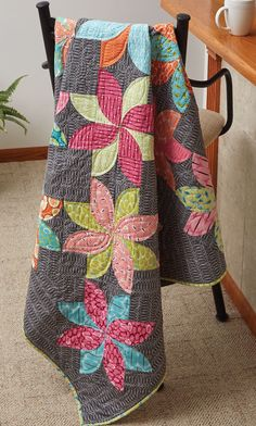 """Using 3"""" curved seam units, designer Emily Bailey arranged them to create a modern floral design for this intermediate level quilt project."""