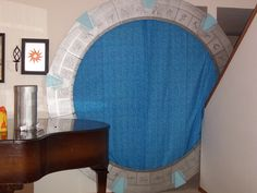 Homemade STARGATE.  Made with cardboard (free from local businesses), LOTS of hot glue for the symbols, fabric, silver spray paint, blue interior paint, duct tape.  Not quite life size (according to the one on the show), but big enough for a themed birthday party.