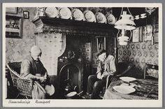 Binnenhuisje Nunspeet. Mensen in klederdracht in een oud interieur met schouw, waaronder een ijzeren open haard tegen een tegelwand. Aan de muur een afbeelding van Leonardo da Vinci's Laatste Avondmaal. Verder een petroleumlamp en een appèlketel boven de vuurplaats.