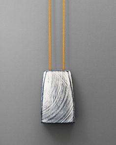 """Julia Turner """"Tracks"""" pendant, 2015. Walnut, paint, nylon cord. 2 1/2 x 1 1/4 x 3/4 in (6.5 x 4 x 2 cm)."""