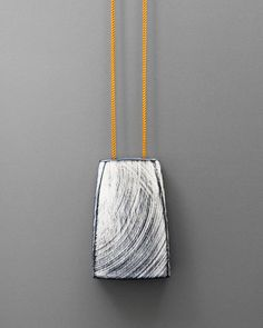 "Julia Turner ""Tracks"" pendant, 2015. Walnut, paint, nylon cord. 2 1/2 x 1 1/4 x 3/4 in (6.5 x 4 x 2 cm)."