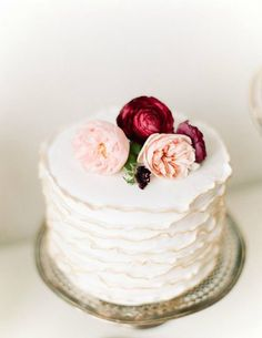 ruffled white cake with blush and burgundy flowers