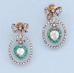 A PAIR OF BELLE EPOQUE EMERALD AND DIAMOND EAR PENDANTS Each designed as a collet-set diamond hoop suspending a diamond and emerald heart-shaped cluster to the bow surmount, mounted in silver and gold, circa 1905.