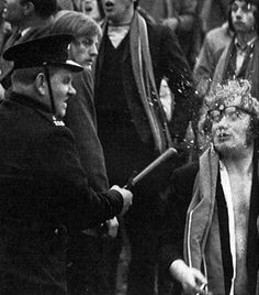 A man's glasses explode after he is hit by a police officer. C. 1960s