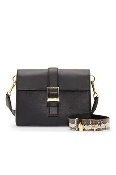 The Lowe by Louise et Cie is a buckle-detailed shoulder bag. Classic and sophisticated with luxe minimalism and distinctive design. Add structure to your ensemble with the tidy styling of a boxy messenger bag. Decorative buckle hardware positioned on the flap is complemented by a congruent buckle on the python-printed shoulder strap. This snappy purse isn't all business; octagon hoops support the strap clips and introduce a charming whimsy to the smart accessory. Made of black multi…