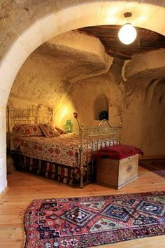 A cave bedroom suite features a brass bed, bought off the back of a truck for about $200, a nomadic tent band used as a dust ruffle and a Beluch tribal bag used as a pillow atop a sandik, or wooden storage chest in the home of Laura Prusoff and Nurettin Mantar in Ortahisar, Turkey.