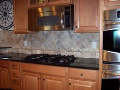 """Timberlake Maple Spice cabinets with black knobs.  These are the exact cabinets I have in my kitchen.  I love the black counter top and back splash with them in this pic!  The back splash is called """"Storm"""" and the counter top is Impala Black granite."""