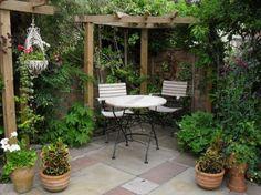 gemütliche Sitzecke im Schatten von der Holzpergola und frischer Begrünung