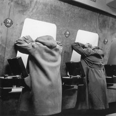 Customers listening to the latest record releases at a listening booth in the…