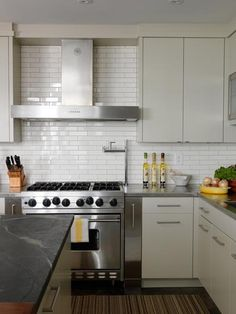 Cameron MacNeil    modern off-white kitchen design with soft gray modern cabinets, white subway tiles backsplash, soapstone counter top, stainless steel counter tops, chrome, hardware, stainless steel appliances, pot filler, gray walls paint color.