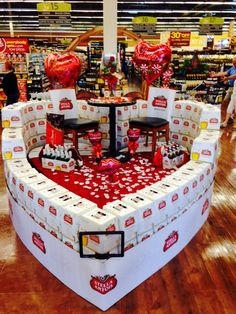 Valentines beer display, heart shaped, romantic setting on top, rose pedals 12pks of stella Artois, front of display. #beerdisplay#creativebeerdisplay#stellaartois#rjcm