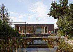 Muddy-toned timber house raised on stilts so it overlooks a swimming pond: http://www.dezeen.com/?p=589747