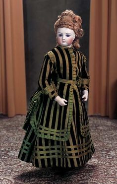 Doll, ca 1860 wearing a fine early silk and velvet striped gown,undergarments,and green leather shoes.