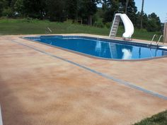 Deck drain was added to help drain storm-water off the concrete surface. Pool deck was stained with a solid color, Tan,  with semi-transparent highlights in Natural Henna & Loden. A Border in Rich Brown (solid) accents the pool coping.
